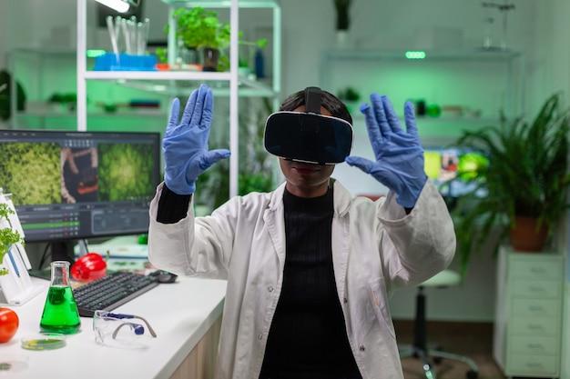 샘플을보고 농업 경제학에 대한 손 제스처를하고 가상 현실을 사용하여 연구를 수행하는 과학자 생물 학자