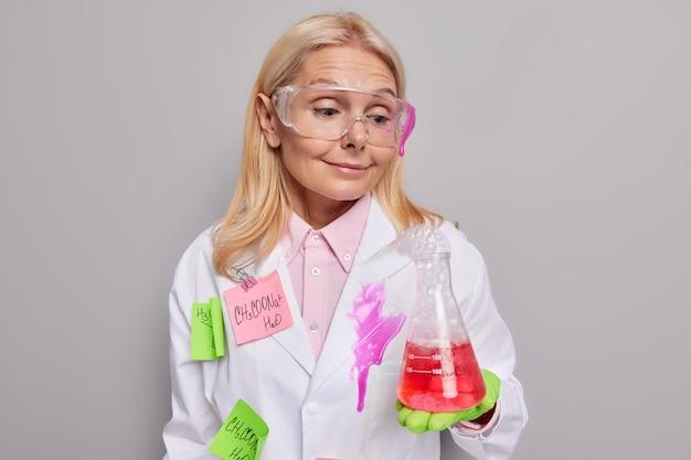 과학자는 연구실에서 실험을 수행합니다. 재료의 화학적 구성을 연구하는 책임이 있는 유리 제품에서 버블링 붉은 고독을 봅니다.
