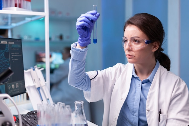 Scientist chemist analyzing a liquid sample and discovering genetic infection with coronavirus
