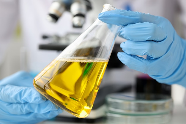 Scientist chemist holding glass flask with yellow liquid in front of microscope closeup quality