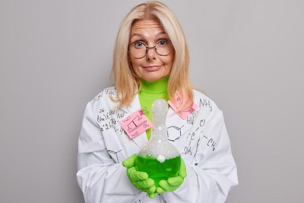 Ученый проводит исследования в лаборатории, проверяет химические реакции, одетый в униформу позы на сером