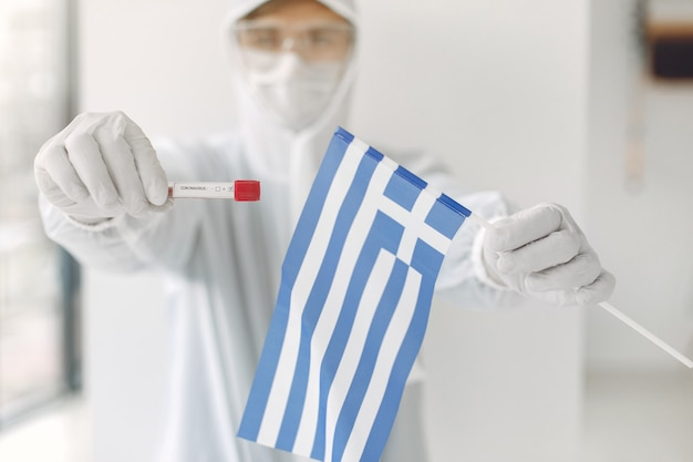 The scientist in coverall suit with a coronavirus sample and greek flag
