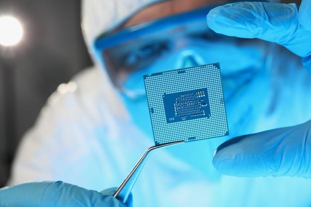 Ученый-разработчик в защитном костюме держит микросхему