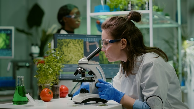 顕微鏡下で植物を分析する科学者の医師