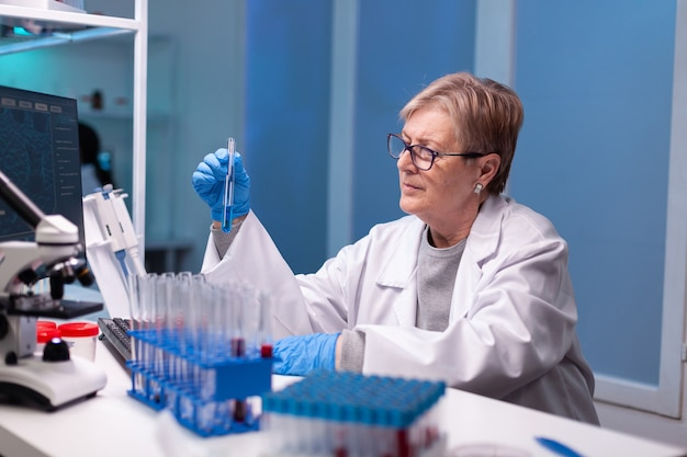 Scientist doctor in white coat discovering genetic infection and analysing a teste tube