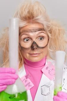 Ученый, одетый в рабочую форму, держит пробирки, смешивает реагенты в колбе, проводит эксперимент в лаборатории, имеет взлохмаченные волосы