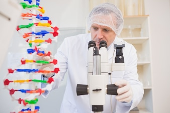 Scientist examining dna helix and looking in microscope