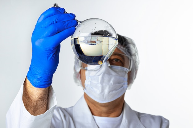 Scientist hands holding some liquid in a glassware in laboratory for analysis