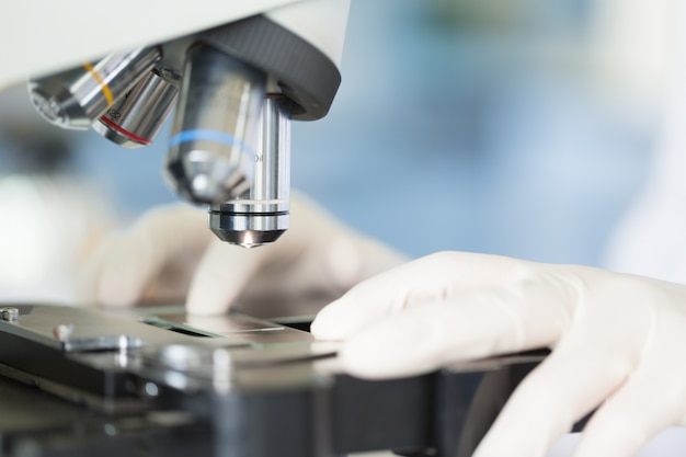 Scientist hands with microscope, examining samples, concept science and technology