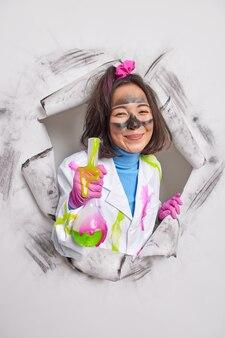 과학자는 녹색 액체가 있는 더러운 얼굴 홀 유리 플라스크를 가지고 있습니다. 실험실 연구는 종이에 의료 코트 포즈를 취합니다