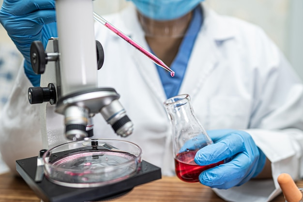 世界の医師のための実験室で感染性の微生物サンプル発生コロナウイルスまたはcovid-19のチューブを保持および分析する科学者。