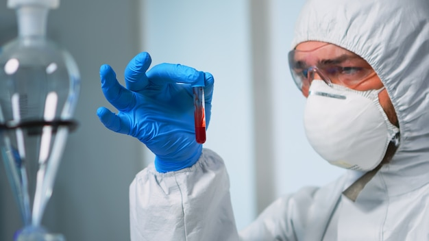 Scientist holding blood sample wearing protection suit analysing virus evolution in laboratory. doctor working with various bacteria and tissue, pharmaceutical research for antibiotics against covid19