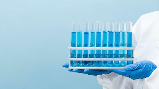 Scientist holding blue chemicals with copy space