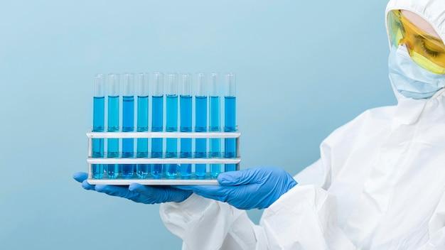 Scienziato che tiene i prodotti chimici blu