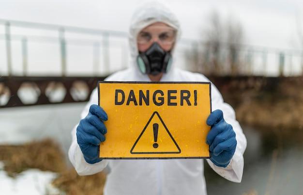 危険標識ミディアムショットを保持している科学者