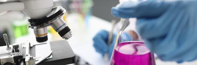 현미경 근접 촬영 화학 교육 앞의 분홍색 액체와 과학자 지주 플라스크
