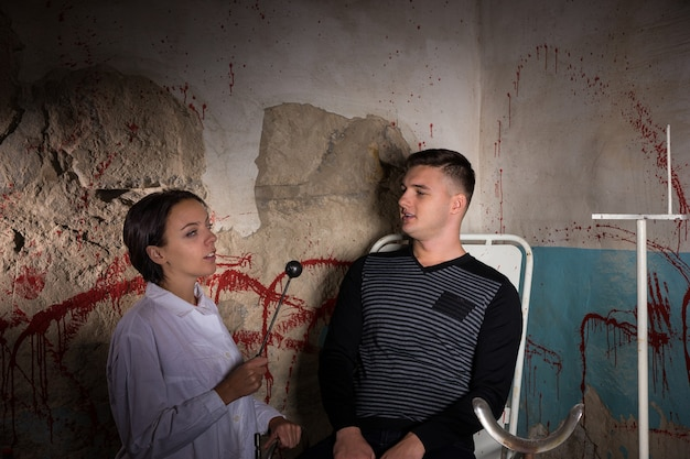 Scientist holding iron medical device in front of patient in dungeon with bloody walls in a halloween horror concept