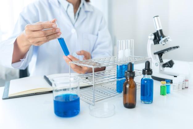 分析に取り組んでいる間、手で試験管を保持している科学者は試験管から青い液体をチェックします