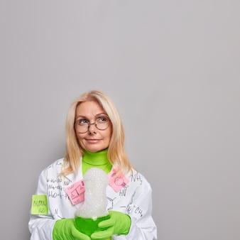 과학자는 녹색 액체가 든 유리 플라스크를 들고 약학적 테스트를 수행하여 메모 메모에 메모를 작성합니다. 회색 벽에 격리된 화학식을 씁니다.