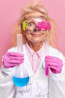 Lo scienziato tiene la fiala e la boccetta con liquido colorato indossa occhiali protettivi sporchi dopo i lavori di esplosione in laboratorio mostra i risultati dell'esperimento chimico isolato sulla parete rosa