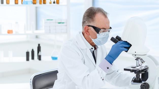 保護マスクの科学者が実験室で研究を行っている
