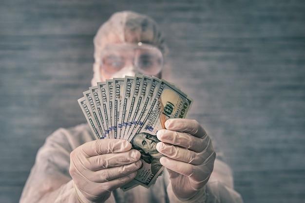 Ученый в защитном костюме, медицинских перчатках и маске держит в руках деньги. грязевые микробы и вирусные бактерии на деньгах.