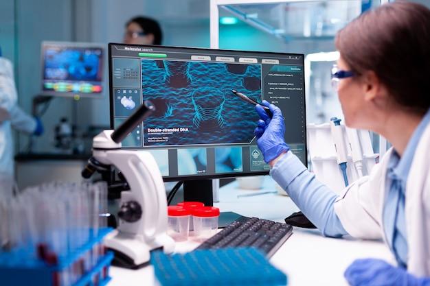 컴퓨터 모니터, 약리학에서 바이러스를 분석하는 생화학 산업 의료 과학자. 새로운 유형의 백신을 개발하고 연구하는 과학 의학 연구실에서 화학 연구 및 분석.