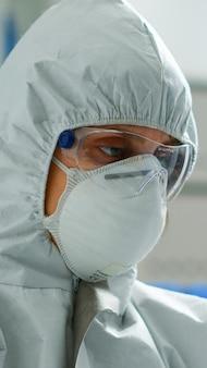 현대적인 장비를 갖춘 실험실에서 튜브의 액체를 분석하는 연구를 하는 작업복을 입은 과학자. covid19 바이러스에 대한 치료 개발을 위해 첨단 기술을 사용하여 백신 진화를 조사하는 생화학자
