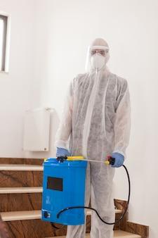 カバーオールスーツの科学者がオフィスビルでコロナウイルスに対する消毒剤を散布します。
