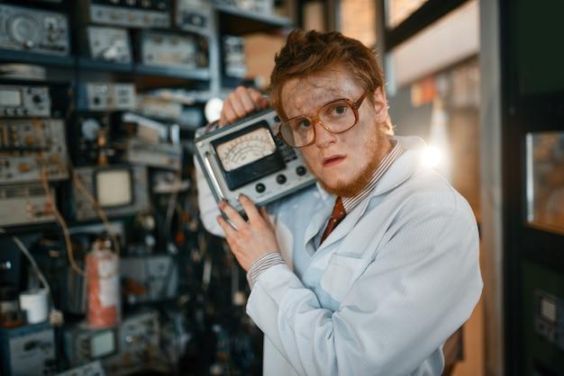 眼鏡の科学者は電気機器を持っています