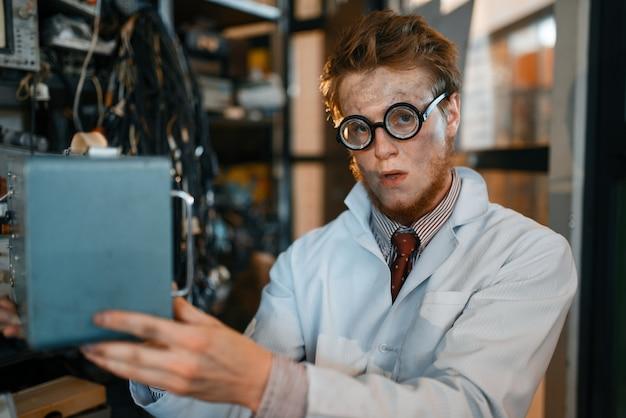 メガネの科学者が電気機器を保持