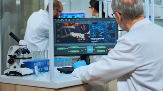 현대적인 장비를 갖춘 실험실에서 컴퓨터에서 일하는 실험실 코트를 입은 과학자. 과학 연구, 바이러스 개발을 위한 첨단 화학 도구를 사용하여 백신 진화를 조사하는 다민족 팀