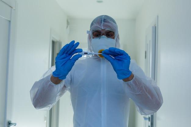 Ученый в защитном снаряжении со скрещенными руками в лаборатории