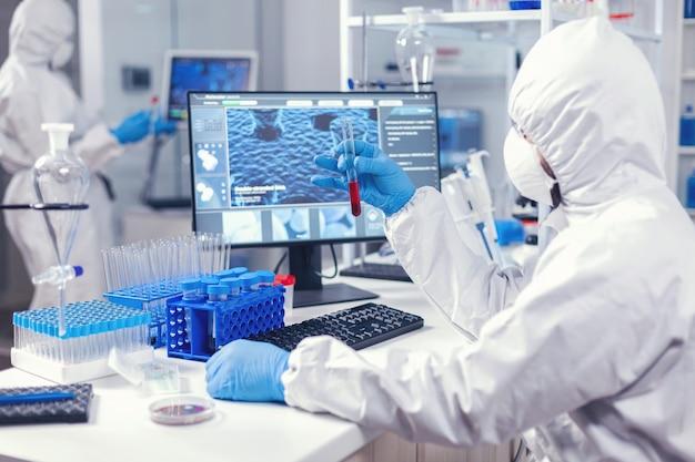 작업복과 얼굴 마스크를 착용한 혈액 검사 튜브를 검사하는 scienec 실험실의 과학자. 다양한 박테리아와 조직을 다루는 의사, covid19에 대한 항생제에 대한 제약 연구.