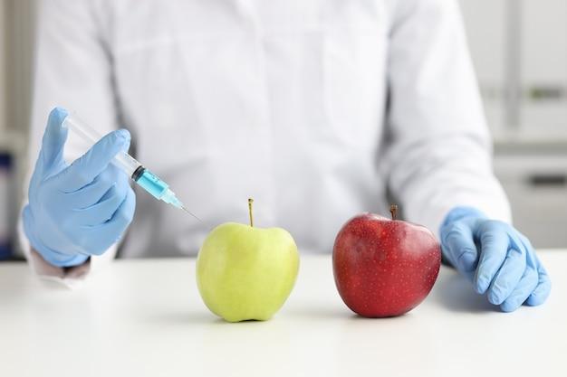 Ученый в белом халате делает инъекцию в зеленое яблоко лабораторных овощей и фруктов