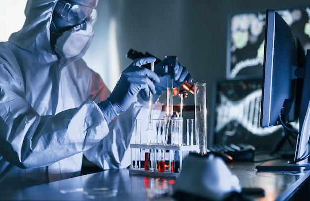 흰색 보호 제복을 입은 과학자가 실험실에서 코로나 바이러스 및 혈액 튜브와 함께 작동합니다.