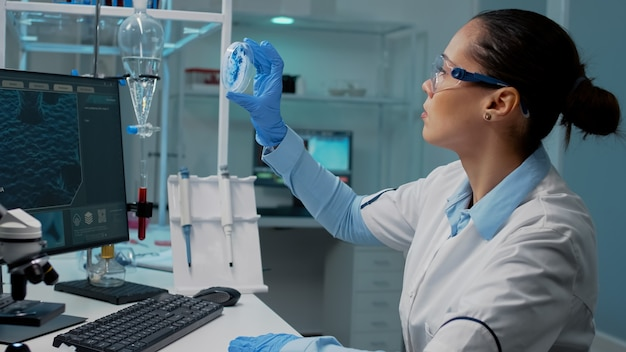 Scientist in laboratory analyzing petri dish with liquid bacteria
