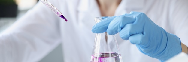 Scientist in laboratory holds transparent flask of liquid and digs purple reagent into it