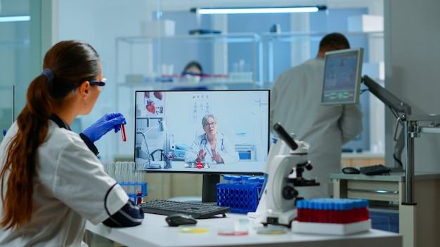 Scientist listening professional doctor on video call, discussing during virtual meeting in medical research laboratory. chemist examining vaccine evolution using high tech researching treatment