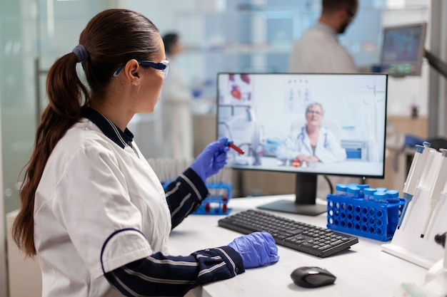 Scientist listening professional doctor on video call, during virtual meeting in medical research laboratory