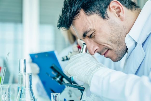Scientist look into microscope while making medical test in science laboratory