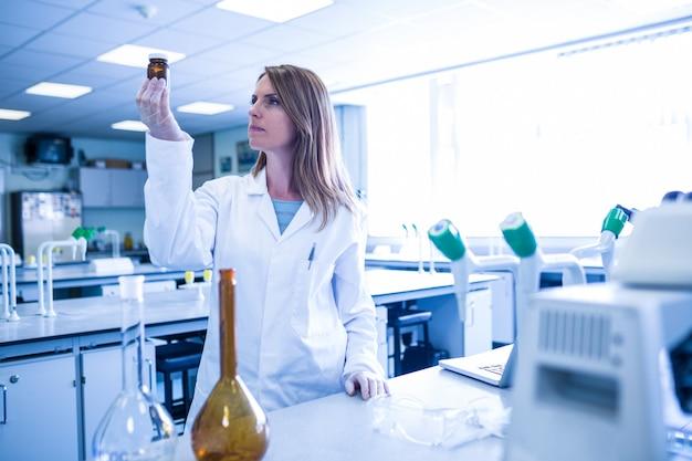 Scientist looking at beaker of chemical