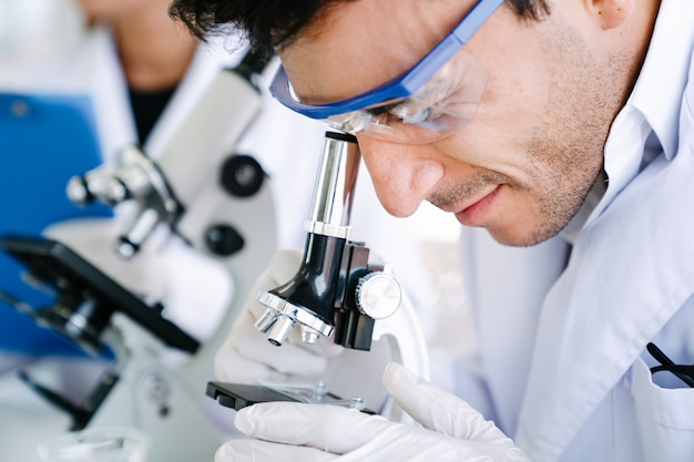 Scientist looking into microscope for checking medical test in science laboratory