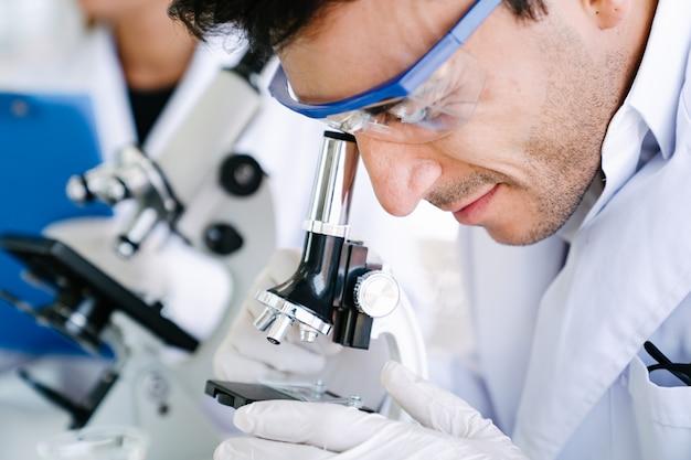 Ученый смотрит в микроскоп для проверки медицинского теста в научной лаборатории