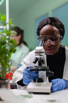 Scientist looking at leaf sample under medical microscope while writing biological expertise on notepad