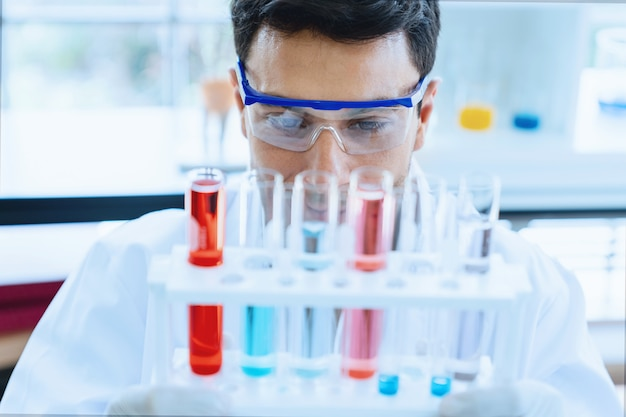 Scientist looking at medical test in glass tube while doing research in scientific laboratory