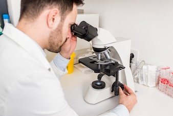 Scientist looking through a microscope in a laboratory at hospital