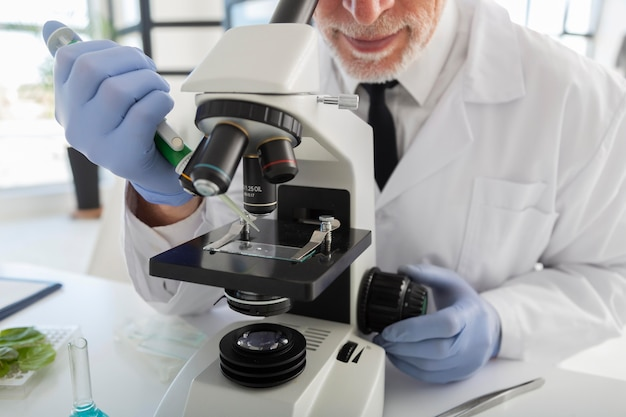 Scienziato che osserva tramite il microscopio da vicino