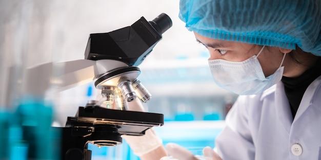 Ученый, смотрящий через объектив научного микроскопа в лаборатории, ученый, проводящий исследования в области медицины, биотехнологии, биологии или химии, врач, анализирующий работу в лаборатории медицинской микробиологии