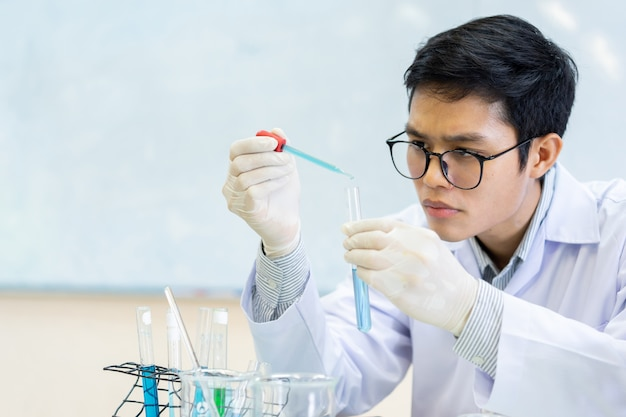 Scientist man hold test tube flask and blending scientific liquid solution at laboratory